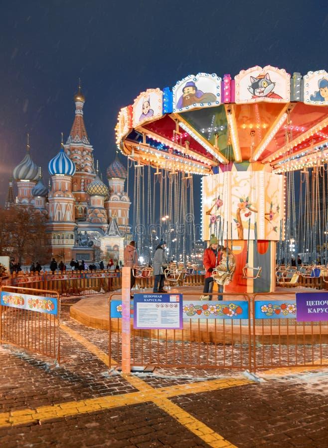 莫斯科,俄罗斯,2017年12月5日:与新年树的圣诞节市场和在红场的减速火箭的转盘马,之间 免版税库存照片