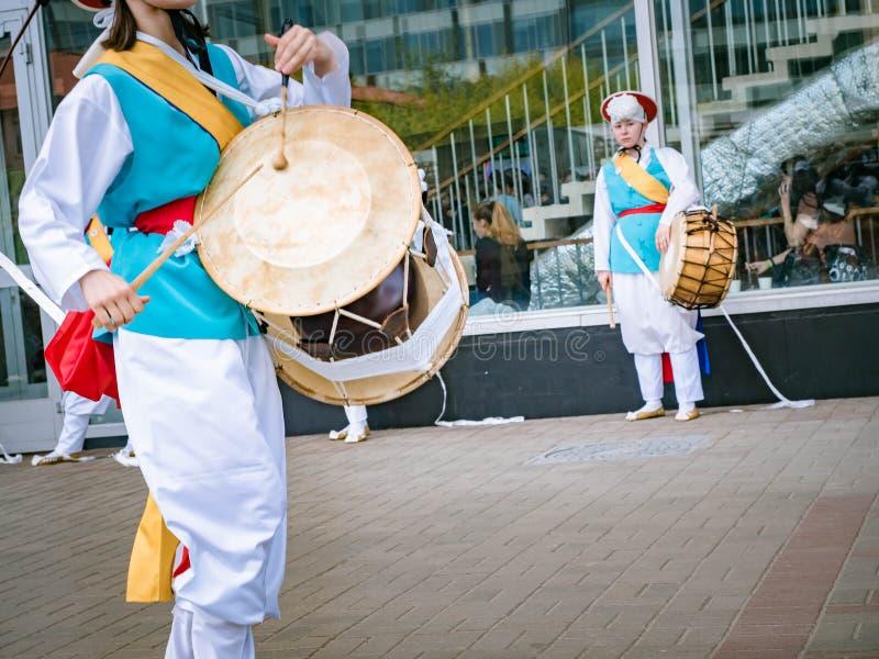 莫斯科,俄罗斯, 2018年7月12日:在韩国传统撞击声乐器Janggu二重带头的鼓的音乐家戏剧与 免版税库存照片