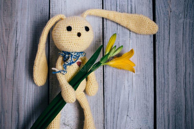 莫斯科,俄罗斯- 06 05 2018年:与百合花束的玩具野兔在木背景,婴孩的一件礼物的 库存照片
