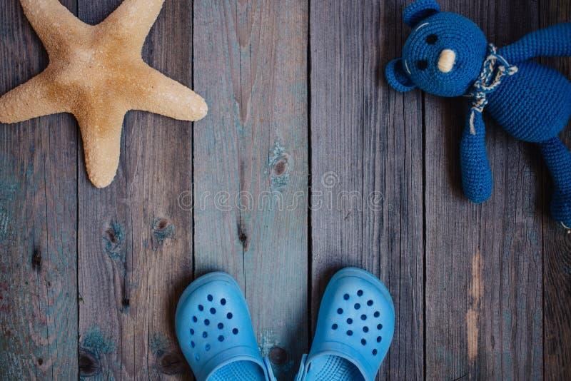莫斯科,俄罗斯- 05 28 2018年:婴孩海滩拖鞋海星女用连杉衬裤涉及木桌 免版税库存图片