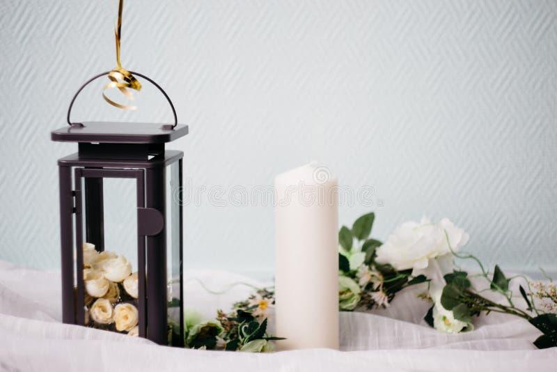 莫斯科,俄罗斯- 06 10 2018年:有白玫瑰、蜡烛和花的黑金属灯在轻的背景,家庭装饰 免版税库存图片