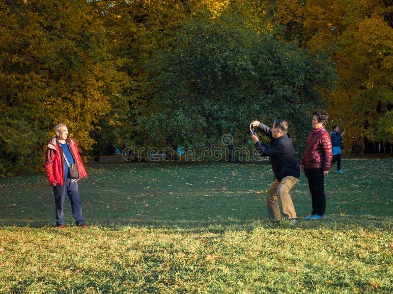 莫斯科,俄罗斯- 2018年10月11日:中国游客走秋天公园 年长亚裔人民拍在的照片 库存图片