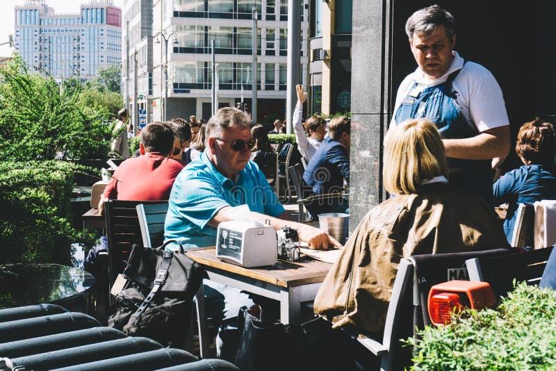 莫斯科,俄罗斯- 2019年5月27日:咖啡馆客人在莫斯科做与一位侍者的命令 免版税图库摄影