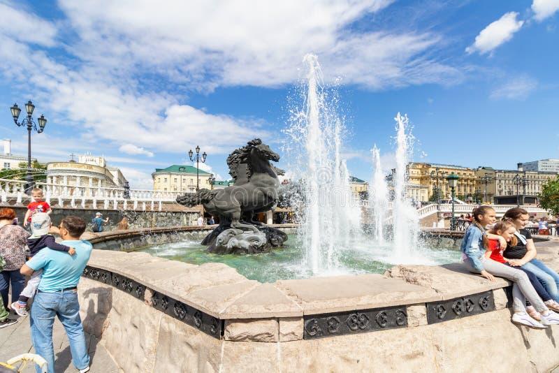 莫斯科,俄罗斯- 2019年6月02日:在喷泉喷泉附近的游人在驯马场广场在莫斯科在晴朗的夏天早晨 免版税库存照片