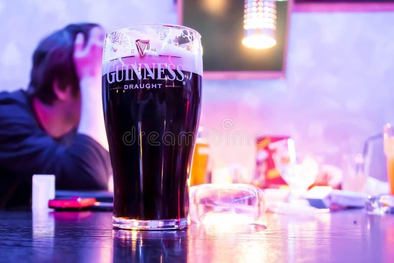 莫斯科,俄罗斯- 2019年5月25日:在酒吧的桌上是一个杯子黑暗的吉尼斯啤酒壮健草稿 以a为背景 库存图片