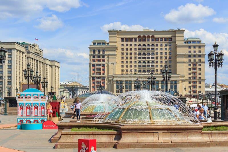莫斯科,俄罗斯- 2018年6月03日:在Manezhnaya的喷泉摆正反对四季酒店和杜马大厦在晴朗的总和 免版税库存照片