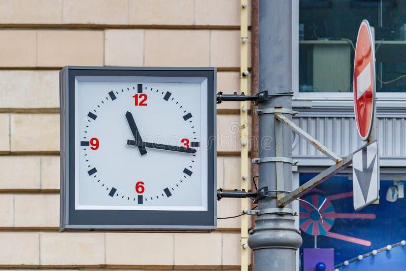 莫斯科,俄罗斯- 2019年6月02日:垂悬在大厦特写镜头砖墙背景的一根杆的模式街道时钟  库存图片
