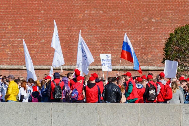 莫斯科,俄罗斯- 2019年5月01日:有旗子的在Kremlevskaya堤防的人和横幅去在红色的劳动节示范 免版税库存照片