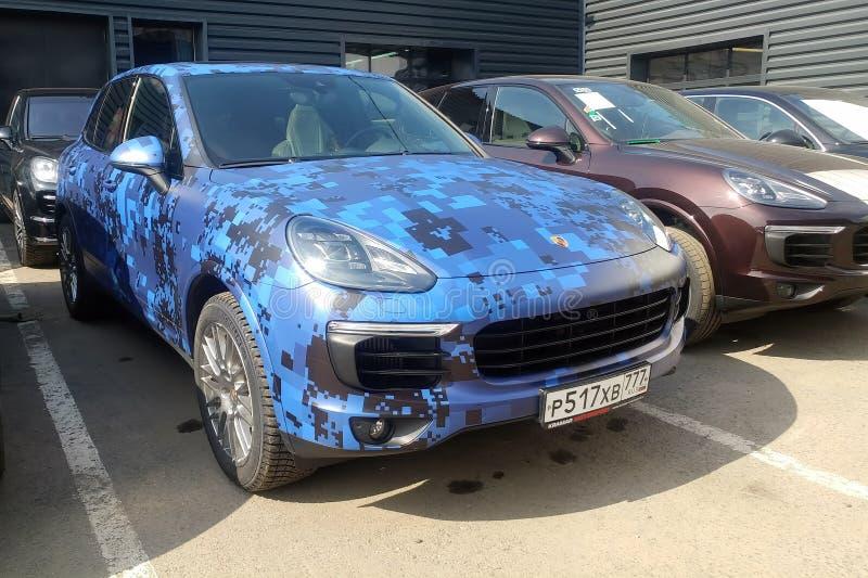 莫斯科,俄罗斯- 2019年5月09日:蓝色伪装保时捷卡宴在街道上停放了 汽车在色的保护膜被包裹 免版税库存图片