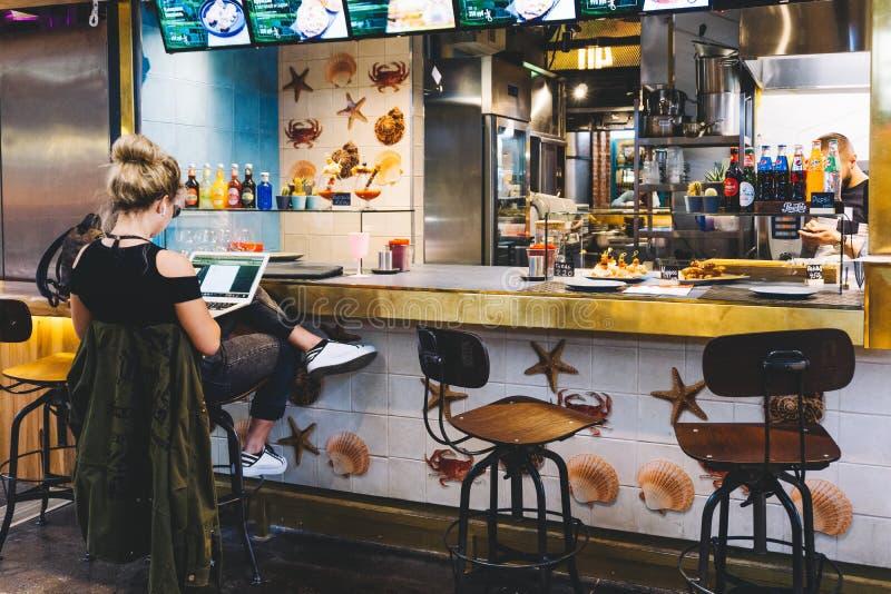 莫斯科,俄罗斯- 2019年5月24日:计算机的年轻女人在咖啡馆 o 库存图片