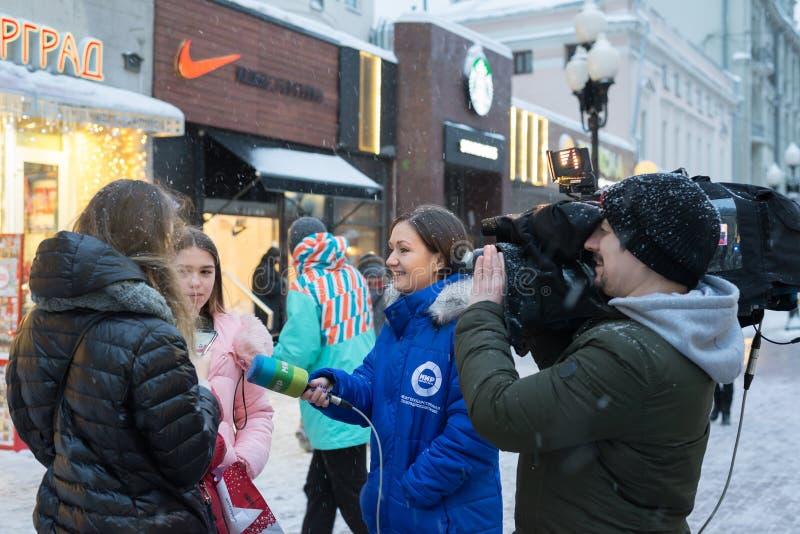 莫斯科,俄罗斯- 2018年2月11日 电视的通讯员和与路人的无线电公司Mir作为采访老Arbat的 免版税库存图片