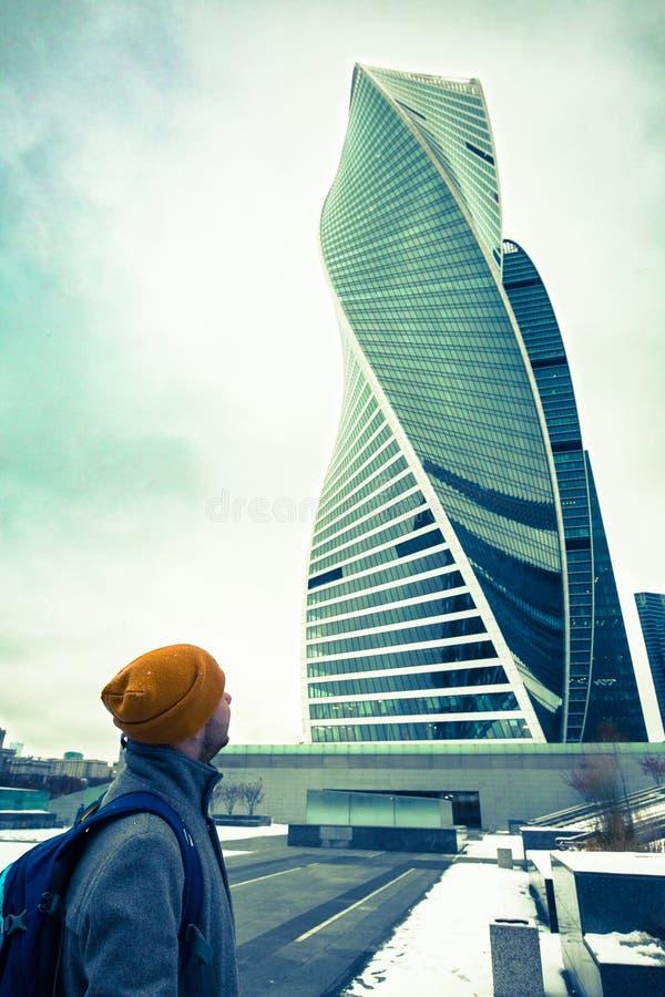莫斯科,俄罗斯- 2016年11月5日:供以人员看摩天大楼,在多云期间的现代大厦的外套、帽子和背包的旅客 库存图片