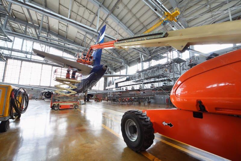 客机苏航尾巴修理在飞机棚 免版税库存图片