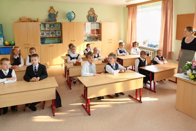 Dima, Anya, Nastya,八岁在教室在学校 免版税库存照片