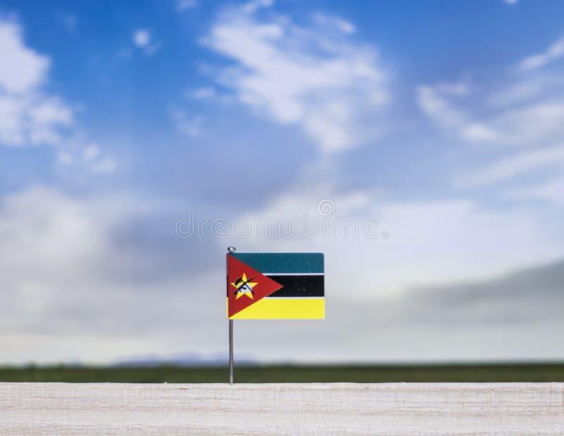 莫桑比克的旗子有浩大的草甸和天空蔚蓝的在它后 库存图片