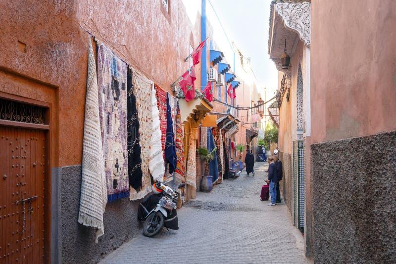 莫罗科市马拉喀什老城带地毯店的狭窄街道 免版税库存图片