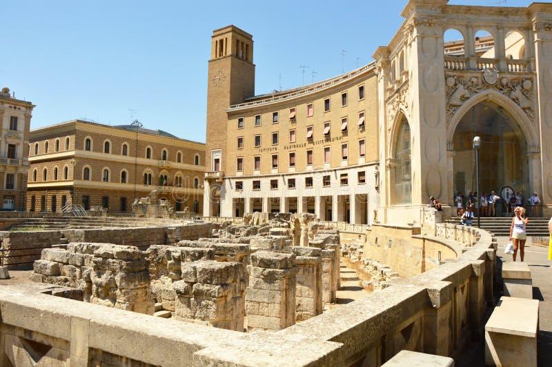 莱切,意大利- 2017年8月2日:有Sedile和伊娜Istituto Nazionale delle Assicurazioni的宫殿的罗马圆形剧场 免版税库存照片