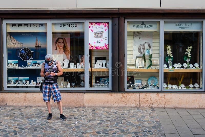 莱奥本,施蒂里亚,奥地利- 2018年8月06日:人在边路在商店窗口和神色站立在电话 免版税图库摄影