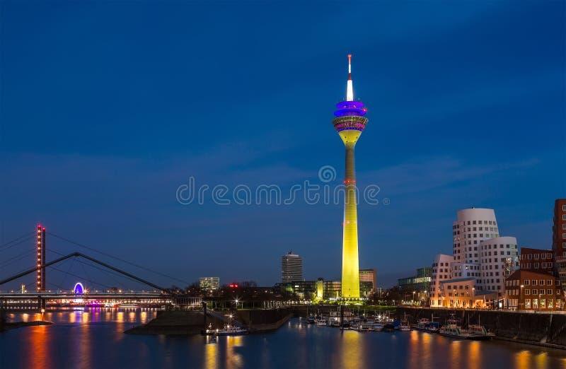 莱茵河五颜六色的夜场面在晚上在杜塞尔多夫 在软的夜光,北威斯特法伦,德国的Rheinturm塔 免版税库存图片