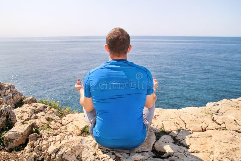 莲花坐的一个适合人在海滨 做瑜伽的年轻健身人户外 免版税库存照片