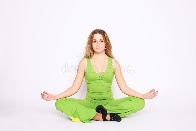 莲花姿势俏丽的坐的妇女年轻人 免版税库存照片