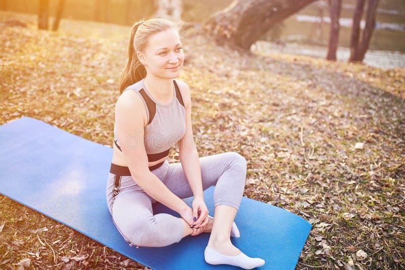 莲花姿势的女孩在瑜伽席子在公园 库存图片