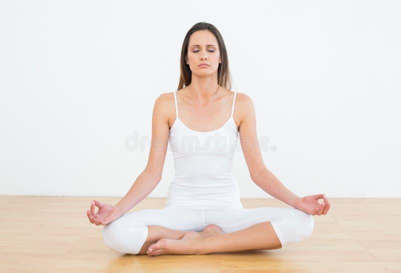 莲花姿势的被定调子的妇女在健身演播室 免版税库存照片