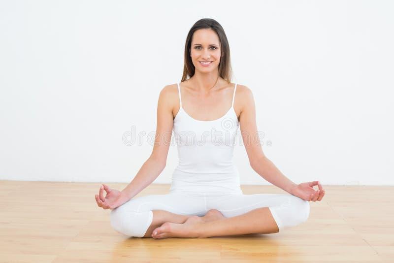 莲花姿势的被定调子的妇女在健身演播室 库存照片