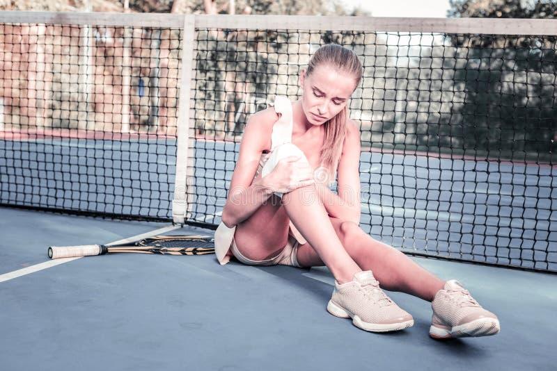 获取体育创伤的悲剧的忧郁女性球员 免版税库存图片