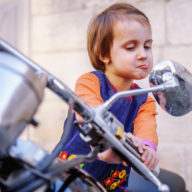 获得一点骑自行车的人儿童的女孩滑稽的画象看在后视镜和在被塑造的摩托车的乐趣 幽默照片 免版税库存照片