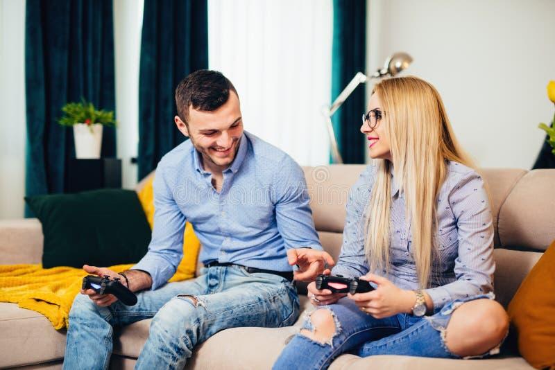 获得与现代技术控制台的乐趣网上,演奏计算机游戏和享受周末的已婚夫妇 库存照片