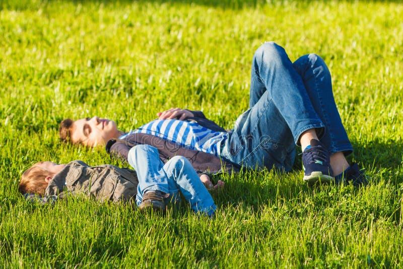 获得两个兄弟、的孩子和的少年乐趣,绿色草甸 库存图片