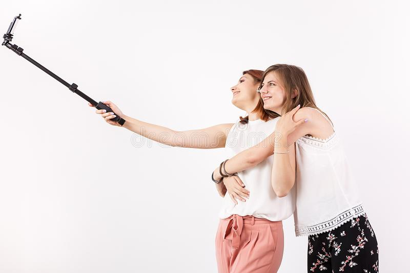 获得两个女性的最好的朋友很多乐趣,当采取一selfie用selfie棍子时 库存图片