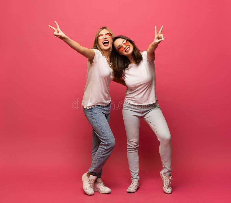 获得两个女性的朋友一起拥抱和乐趣,显示和平姿态,当看照相机,被隔绝在桃红色时 免版税图库摄影