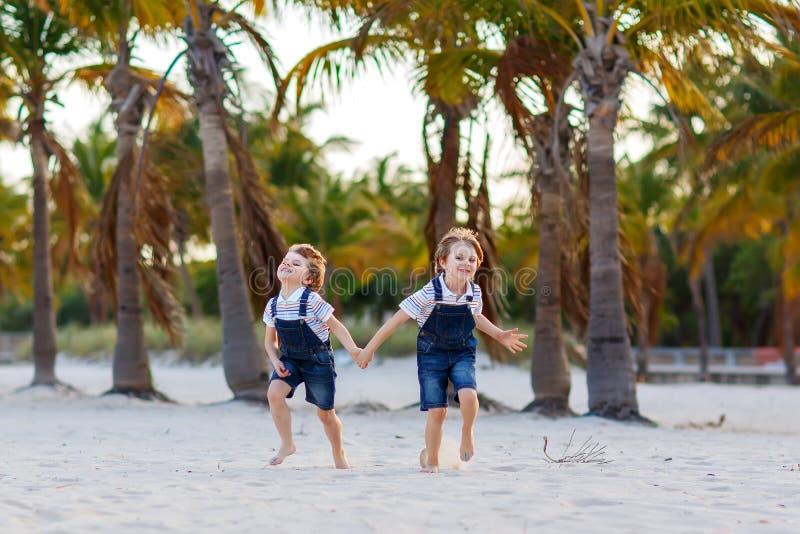 获得两个小孩的男孩在热带海滩,使用愉快的最好的朋友,友谊概念的乐趣 兄弟姐妹兄弟 免版税库存照片