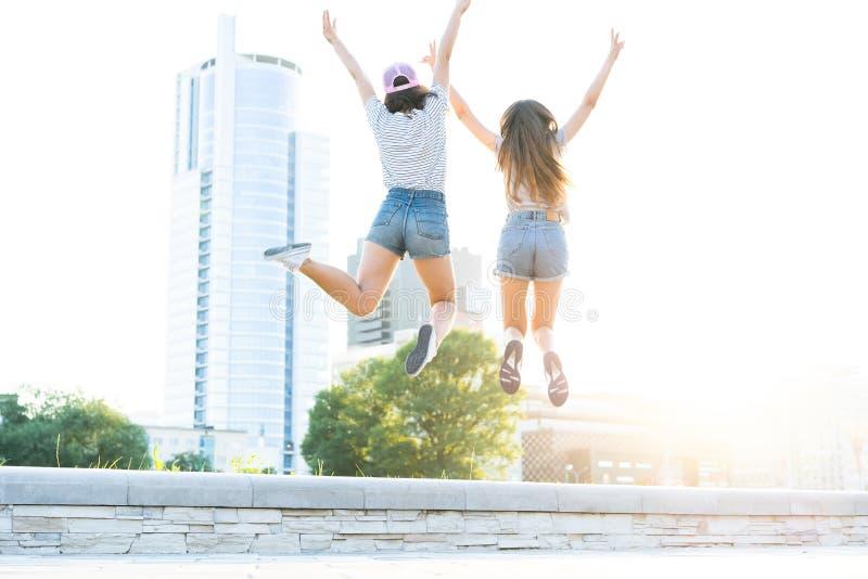 获得两个年轻愉快的行家的女孩乐趣,微笑,笑,跳,走室外在街道上,夏天放松 免版税图库摄影