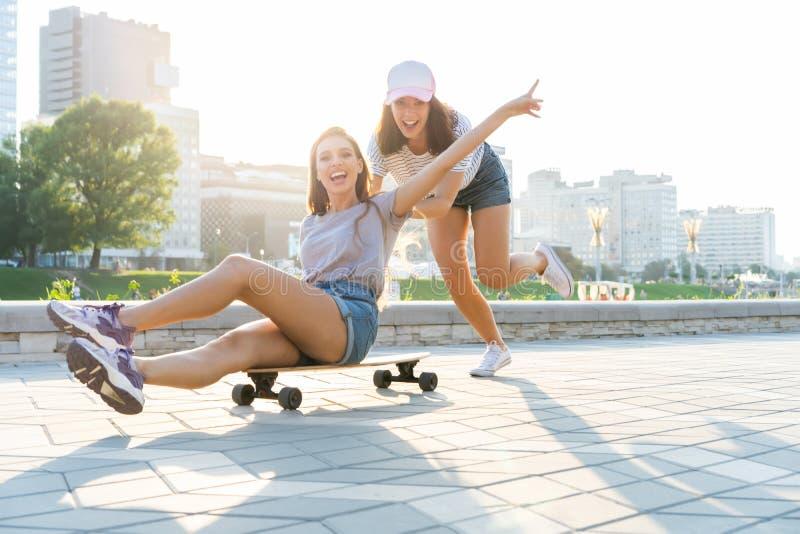 获得两个微笑的女孩乐趣,当乘坐在滑板在公园时 免版税库存照片