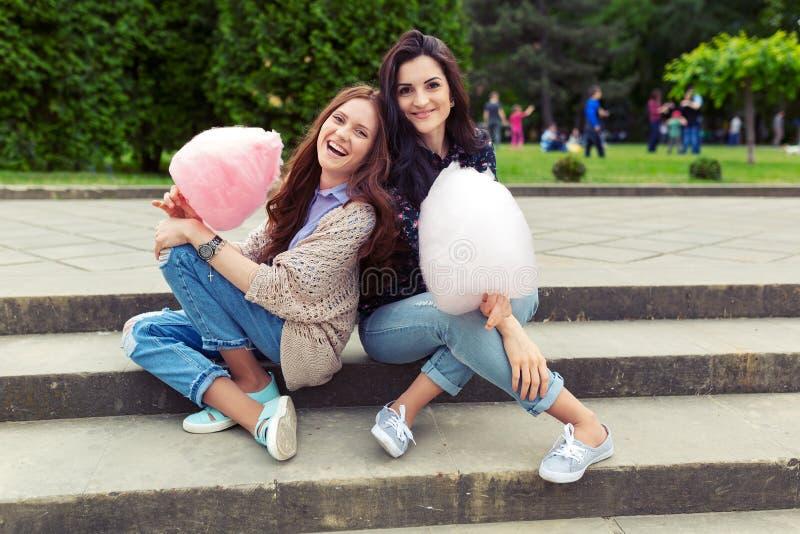 获得两个快乐的女孩乐趣用室外的棉花糖 库存照片