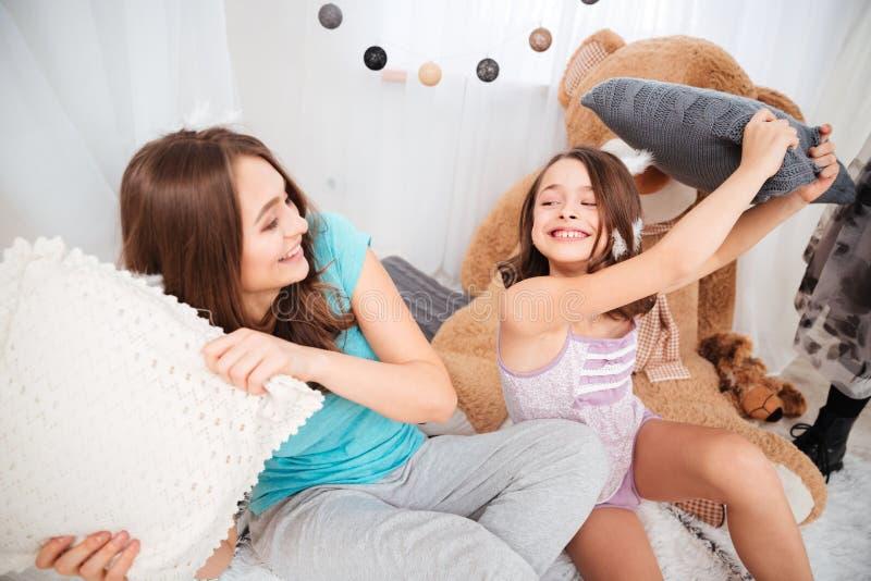 获得两个快乐的姐妹战斗由枕头和乐趣 库存照片