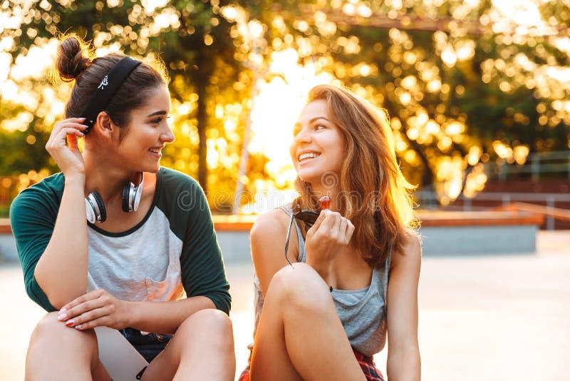 获得两个愉快的女孩乐趣,当坐和谈话时 免版税库存照片