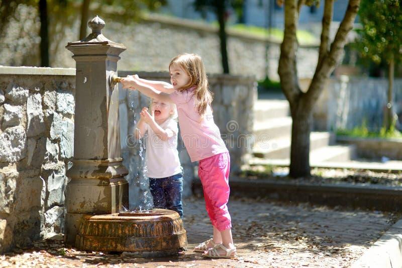 获得两个的女孩与饮用水喷泉的乐趣 免版税库存照片