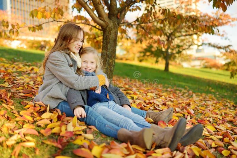 获得两个逗人喜爱的年轻的姐妹乐趣在美好的秋天天 使用在秋天公园的愉快的孩子 会集黄色秋天的孩子 库存照片