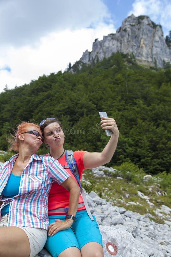获得两名俏丽的妇女做duckface和拍selfie照片的乐趣在山峰 库存图片