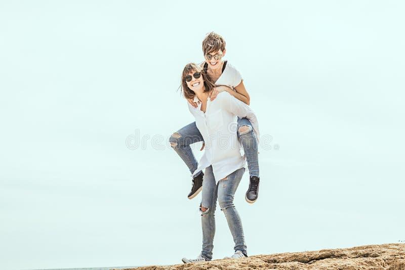 获得两名的妇女在海滩的乐趣 免版税库存照片