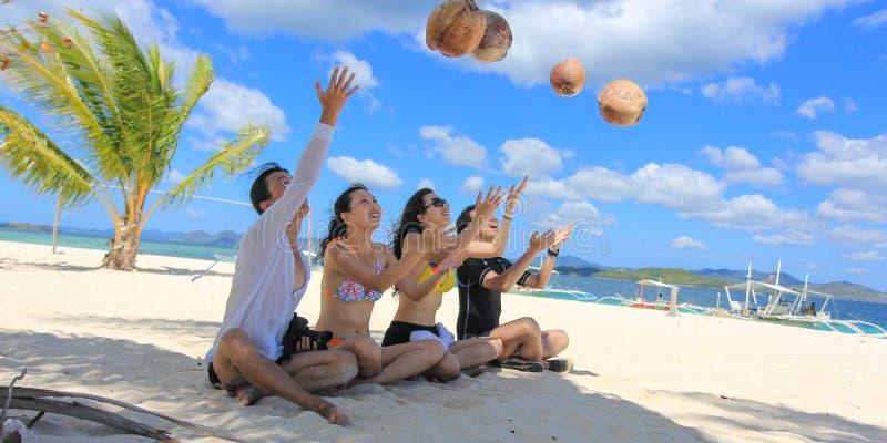 获得两对愉快的年轻的夫妇在热带白色海滩的乐趣 免版税库存照片