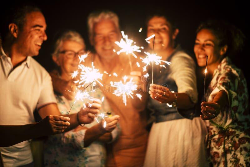 获得乐趣一起庆祝除夕的人或与闪闪发光的生日点燃和在友谊的烟花室外在 库存照片