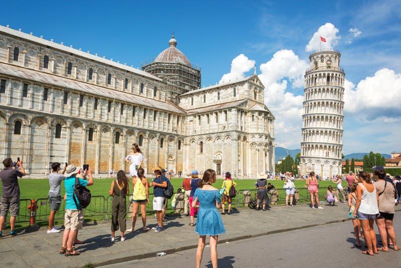 获得乐趣和为比萨照相的斜塔人们在托斯卡纳意大利 免版税库存照片