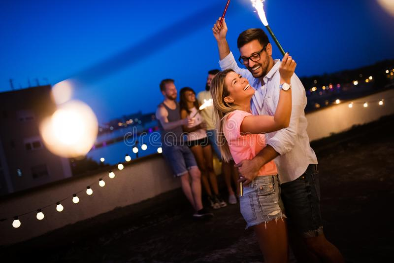 获得乐趣和享受党的愉快的年轻跳舞的夫妇在夏天 免版税库存照片