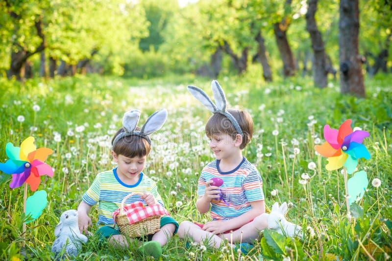 获得乐趣和使用用复活节彩蛋的孩子 两个快乐的男孩坐草坪在复活节彩蛋以后寻找 库存图片