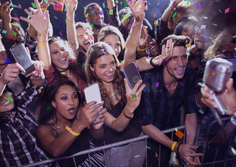 获得乐趣和做照片的人们在与3D五彩纸屑的一个音乐会 库存图片